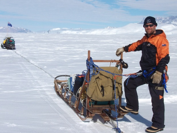 Cliff Atkins, 2012, Nansen Ice Sheet. In 2012 Cliff was doing some research into dust flux on the Nansen Ice Shelf, along the coast of Victoria Land. In this picture he's part of a two man team – one driving the skidoo, one steering the sledge, setting up dust traps across the ice shelf.